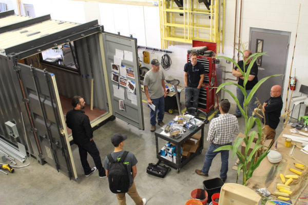 The ZENTX team gathered around the Drydock container bar while it was under construction