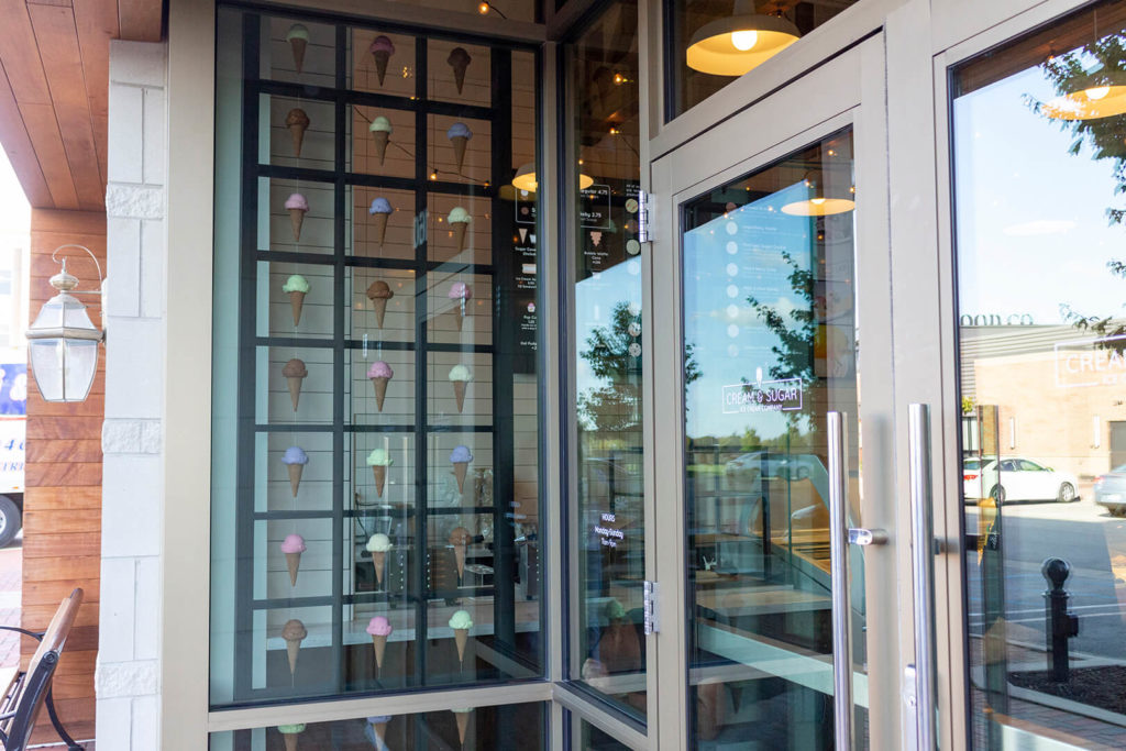 Ice cream display seen through the front window of Cream & Sugar, showing artificial ice cream cones suspended between segments of the frame