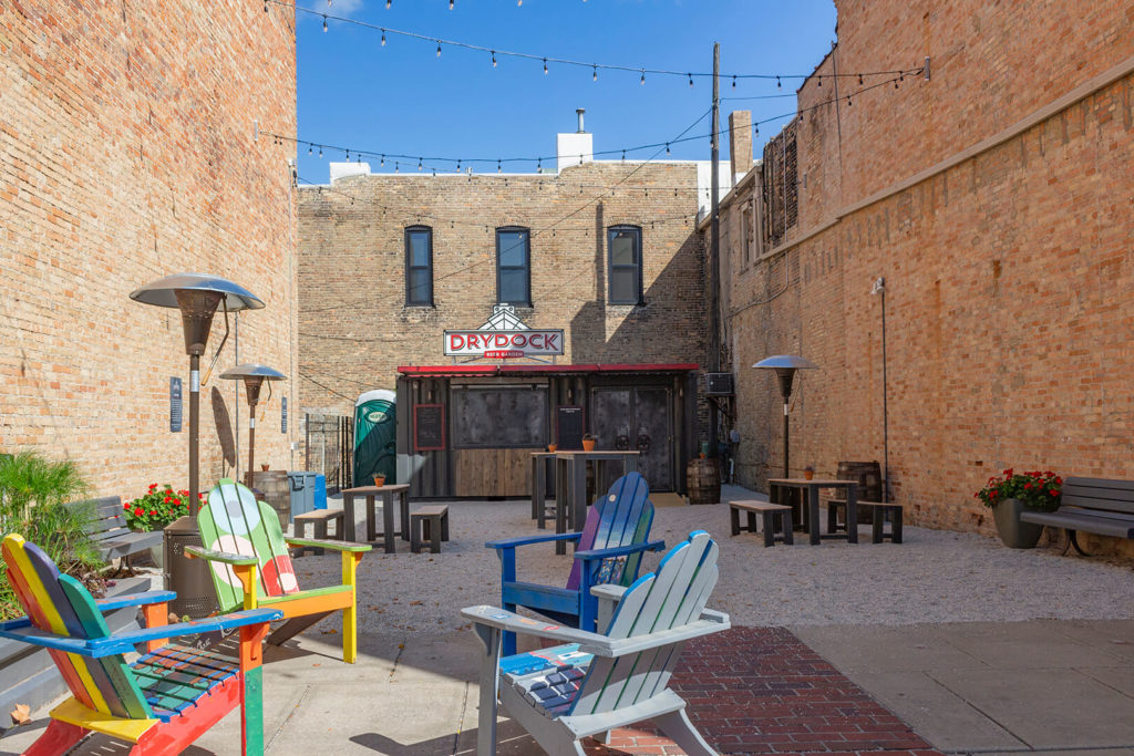 Photo showing the Drydock container bar in its surroundings, with chairs, benches, and tables in the foreground