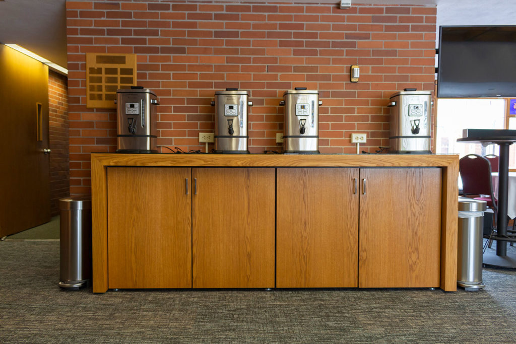 The coffee serving center's cabinets with coffeepots sitting on top