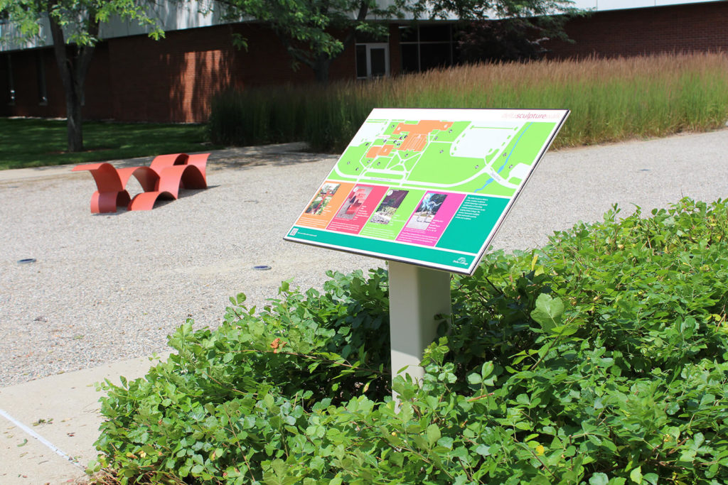 Colorful outdoor wayfinding sign near a piece of sculpture