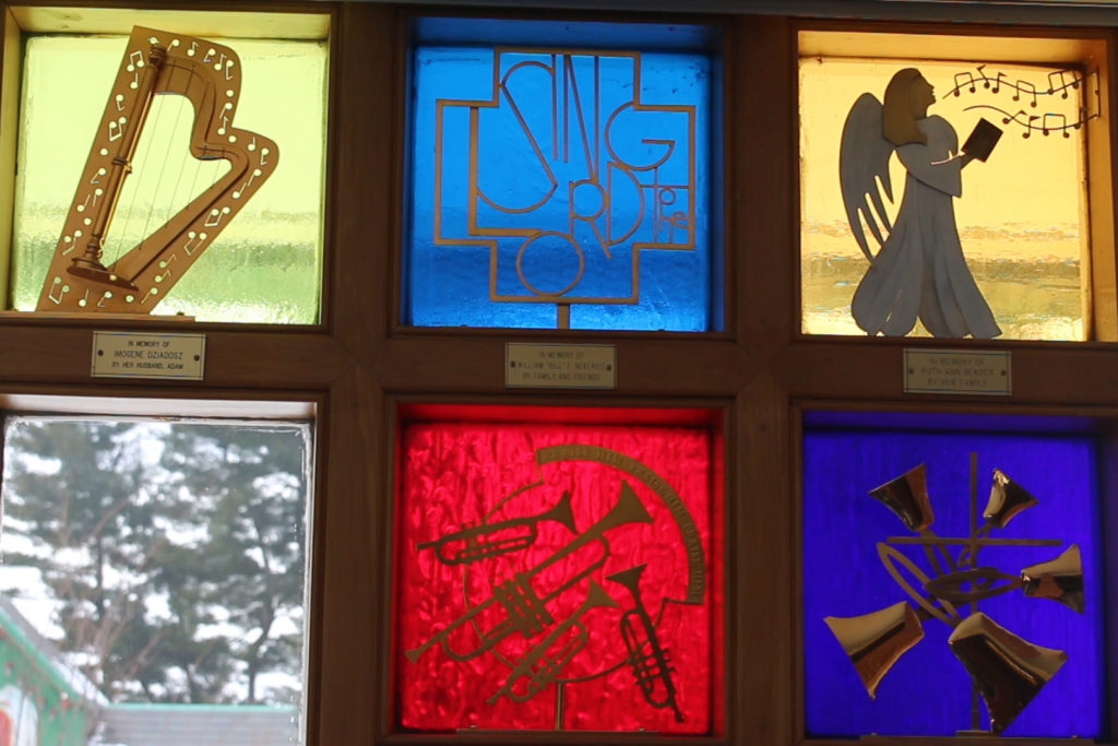 Five square stained-glass windows at First UMC. Each window is a memorial and contains artwork within it