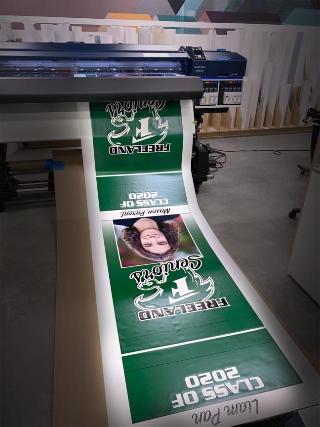 Photo of ZENTX printing custom post banners to celebrate graduates during COVID-19