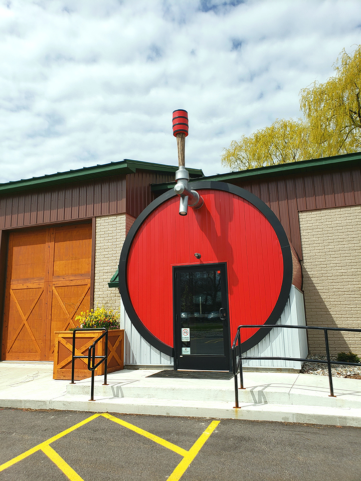 Exterior of a brewery, with an oversize tap handle hanging over the door