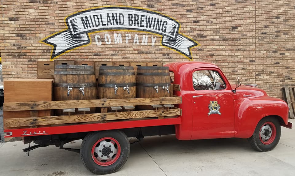 """Red truck carrying wooden barrels, beneath a mural reading """"Midland Brewing Company"""""""