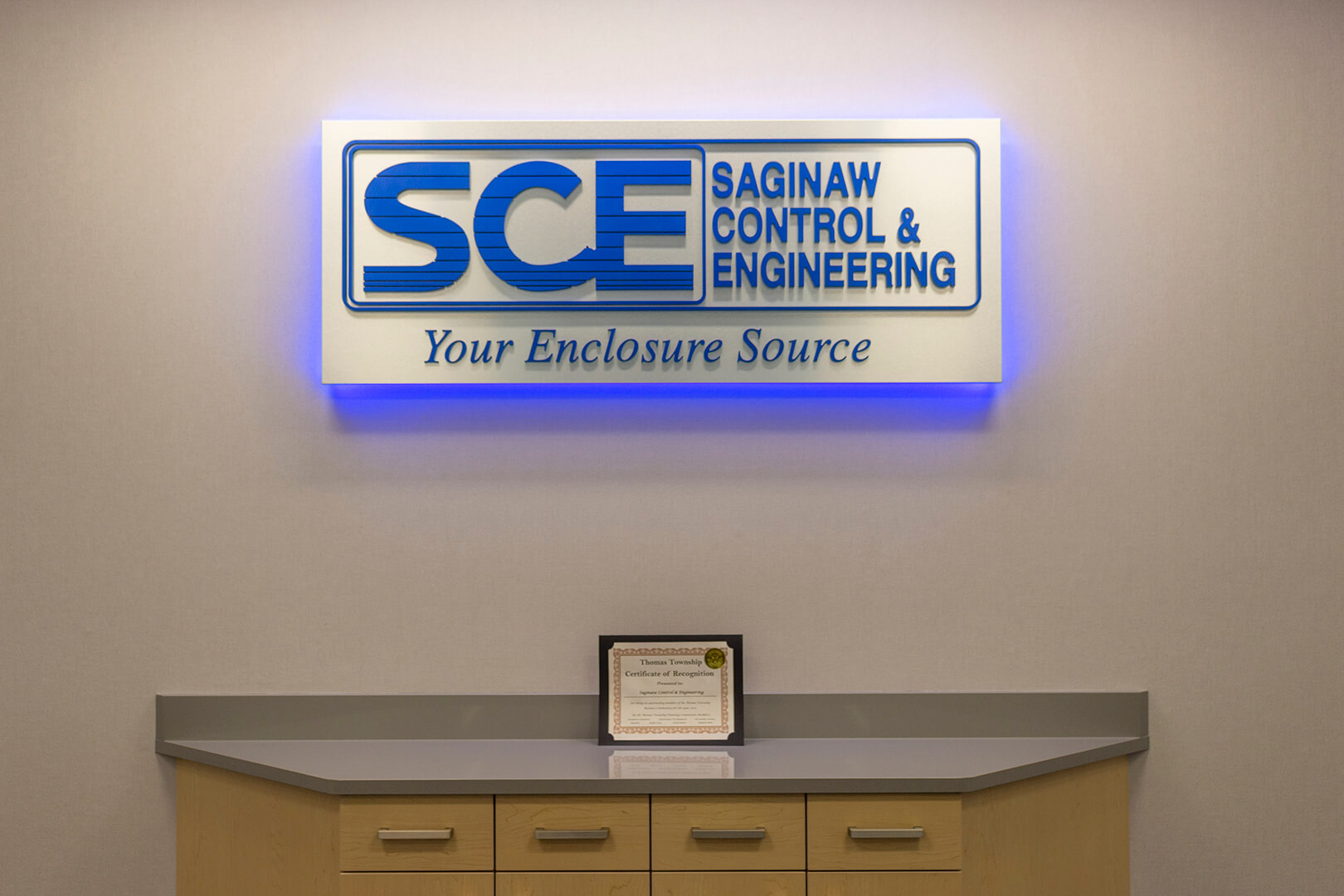 "Sign behind SCE's front desk backlit in blue light; sign reads ""Saginaw Control and Engineering: Your Enclosure Source"""