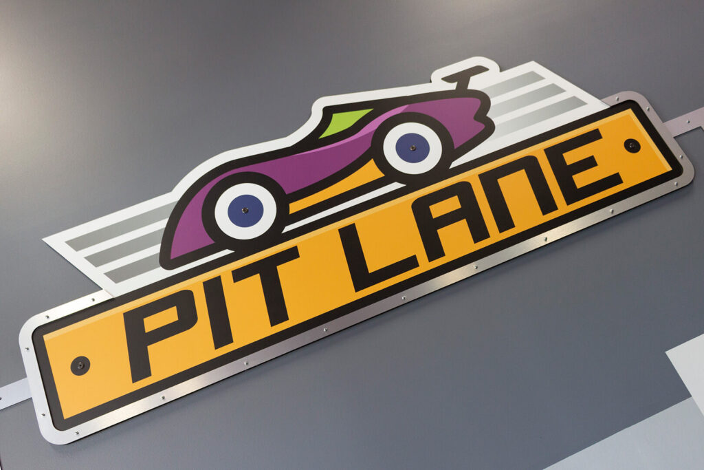 "Sign reading ""Pit Lane"" and showing racecar graphics"