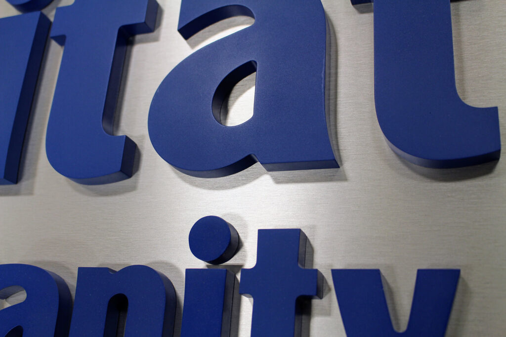 Overhead closeup of dark blue dimensional elements on reflective signage